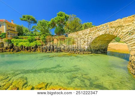 Stone Bridge Of Avenue Rei Humberto Ii Of Italy Over Turquoise Waters Of Cascais On Tagus River Estu