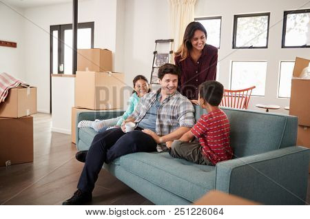 Happy Family Resting On Sofa Surrounded By Boxes In New Home On Moving Day