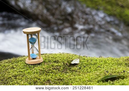 Hourglass On The Green Moss In Front Of Brook