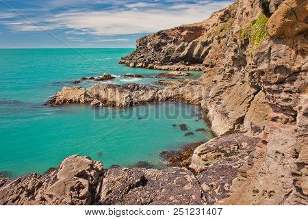 Blue Clear Water Of Bay Near Christchurch City In New Zealand, Walking Along The Rocky Cliffs, New Z