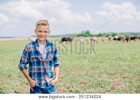 Happy Boy In Checkered Shirt Standing With Hands In Pockets And Smiling At Camera On Field