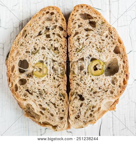 Two Slices Of Olive And Tarragon Bread On A Cracked White Table Board