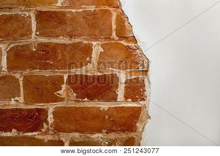 Part of the red brick wall of an old house with a figured pattern of white putty. Background, contrasting texture. A place for a label. poster