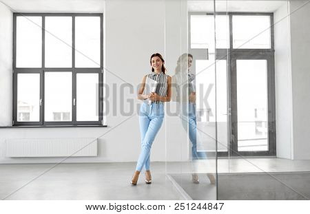 business, people and corporate concept - businesswoman or realtor with folder at office glass wall