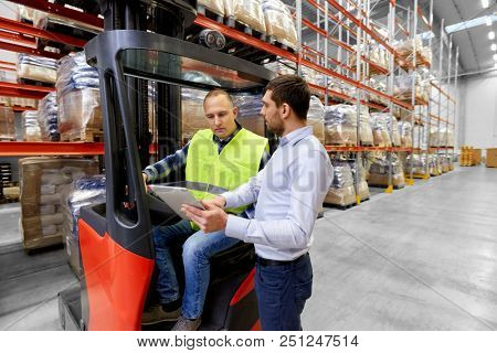 logistic business, shipment and people concept - warehouse worker and businessman with tablet pc computer and tablet pc computer
