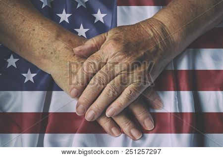 Old Woman's Hands With American Flag, Top View.