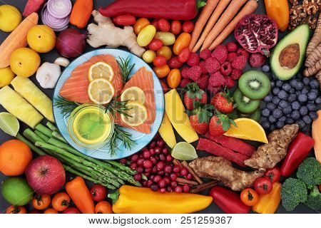 Food for good heart health with fresh fish, fruit, vegetables, herbs, nuts and olive oil. Super food concept with foods high in omega 3 fatty acids, fibre, antioxidants, vitamins and anthocyanins.