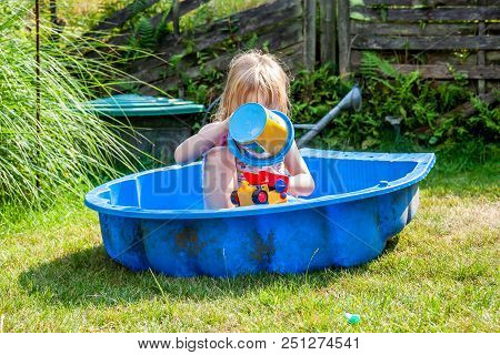Little Girl Enjoying A Hot Summer Day While Usin Her Sandpit As Swimming Pool.