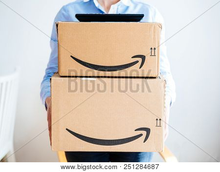 Paris, France - Mar 16, 2018: Vie From The Front Of Happy Smiling Woman Holding Two Large Amazon Pri