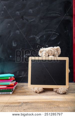 Back To School. Teddy Bear And Blank Blackboard With Frame On Wooden Desk