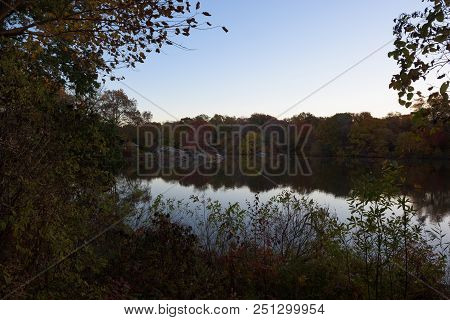 Reflection Of Trees And Foliage In Beautiful Autumn Colors In A Pond In Central Park At Sunrise, New