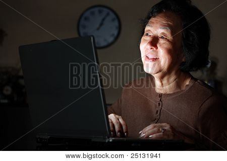 senior asian lady in front of laptop late at night