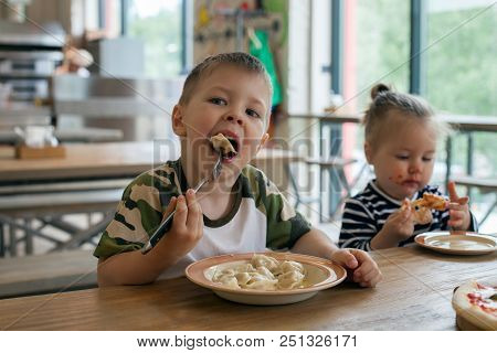 Kids Eat Pizza And Meat Dumplings At Cafe. Children Eating Unhealthy Food Indoors. Siblings In The C
