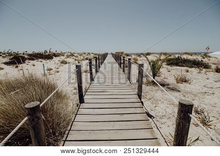 Perspective Of Wooden Walkway Along The Beach On Sunny Summer Day In Algarve, Portuga