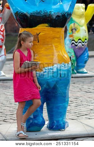 Riga, Latvia - July 26, 2018: United Buddy Bears Exhibition. A Girl With A Tablet In Her Hands Stand