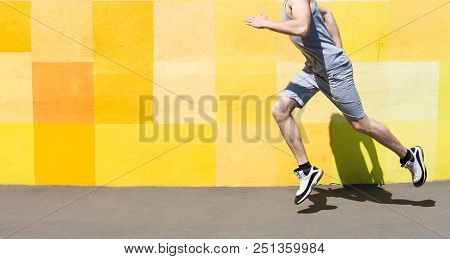 Unrecognizable Athlete Man Running Against Bright Yellow Graffiti Wall, Copy Space, Crop