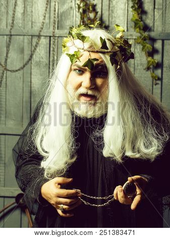 Bearded senior strange mysterious man wizard in long white wig vine crown as Zeus god with medallion on chain indoor on wooden background poster