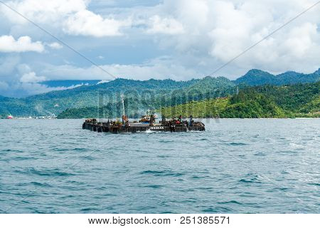 Padang, Indonesia - April 11, 2016 : Small Tugboat Carries Pontoon To Ship That Anchoring In Padang