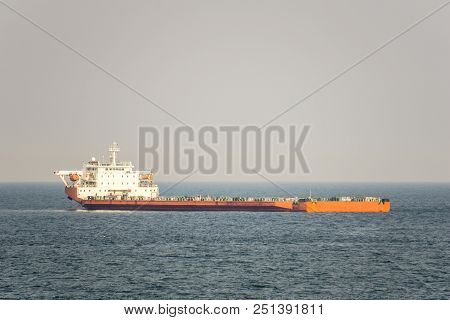 Orange And White Colour Project Cargo Ship Anchors In The Open Sea. Project Cargo Ship Is One Of The