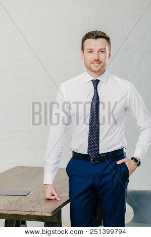 Photo Of Handsome Male Office Worker Dressed In Formal Clothes, Keeps One Hand In Pocket, Other On T