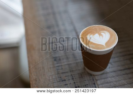 Cappuccino With Beautiful Heart Shape Latte Art In The Paper To-go Cup. Take Away Coffee Concept. Wo