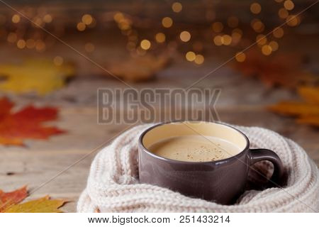 Autumn Background From Cup Of Cocoa Or Coffee In Knitted Warm Scarf On Wooden Table Decorated With F