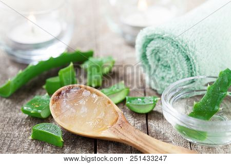 Aloe Vera Gel In Wooden Spoon And Fresh Aloe Vera Leaf On Rustic Table.
