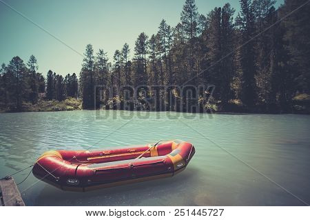 Inflatable Boat On Water On The River Or Lake Near The Shore In A Clear Summer Day, The Bright Refle
