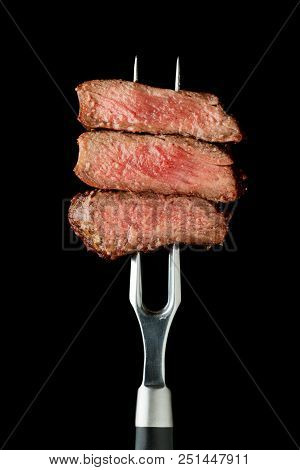 Sliced Beef Steak On Fork Isolated On Black Background
