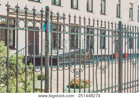 Generic Urban City Apartment Building Exterior With Green Bushes On Front And Steel Decorative Fence
