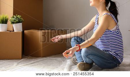 Woman in a new home with cardboard boxes. Woman in the house.
