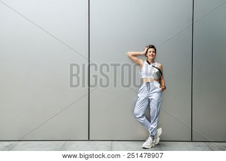 Young attractive woman posing outdoor over silver metal background wall. Beautiful girl. Beautiful caucasian model's portrait.