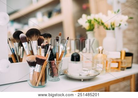 Perfumery And Cosmetics On A Dressing Table With A Mirror And Light, Makeup Brushes And Jewelery On