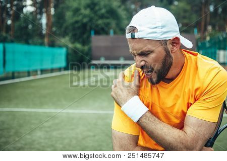 Side View Angry Unshaven Young Man Having Pain In Shoulder While Keeping It With Arm. He Holding Rac