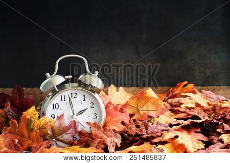 Alarm Clock In Colorful Autumn Leaves Against A Dark Background With Shallow Depth Of Field. Dayligh