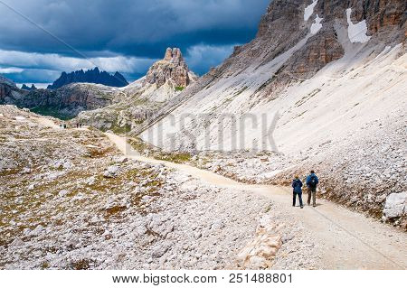 Mountain Hikers With Trekking Poles Walks On The Rocky Path In The Mountains. Nordic Walking Theme.