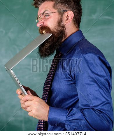 Man hungry for knowledge. Thirst of knowledge. Teacher bearded man bites modern laptop chalkboard background. Hipster teacher wear eyeglasses and necktie bites laptop. He needs new information. poster
