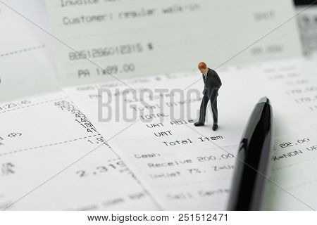Business Expenses, Cost Or Payment Concept, Miniature Businessman Figurine Standing And Checking On