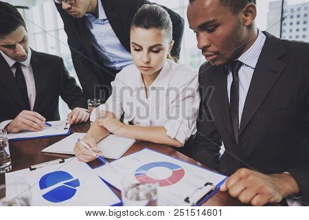Multiracial Team Of Business People Sitting In Office And Discussing Infographic On Table. Brainstom