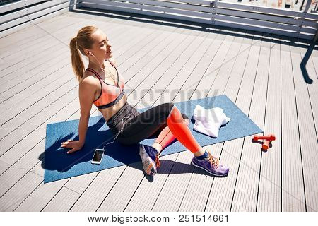 Top View Of Happy Sportswoman Having Good Time While Resting After Exercising With Weights. She Is S