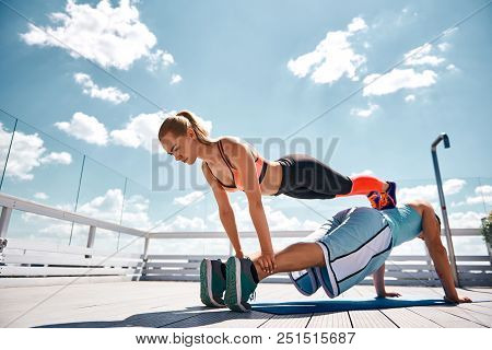 Strong Man Is Staying In Plank And Girlfriend Is Doing Same By Leaning On His Back. They Are Having