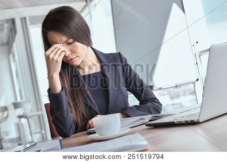 Businesswoman At Office Alone Sitting At Table Working On Laptop Lookiing Down Having A Headache Unh