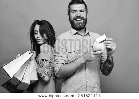 Man With Beard Holds Credit Card And Money Box. Couple In Love Holds Shopping Bags On Green Backgrou