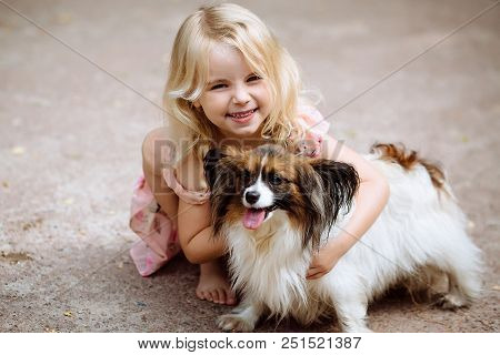 Happy Little Girl With A Dog Standing On The Road In The Park. Cute Little Girl Hugging A Dog, Smili