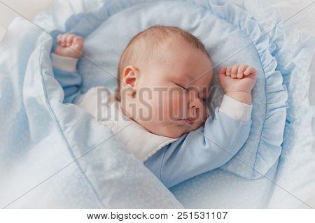 Baby's Restful Sleep. Newborn Baby In A Wooden Crib. The Baby Sleeps In The Bedside Cradle.