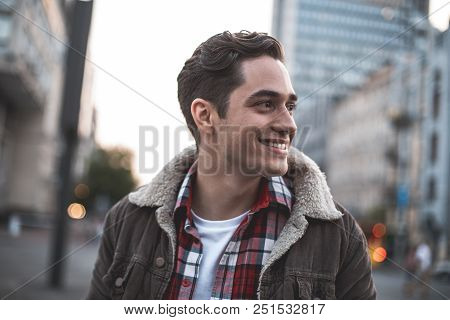 Side View Of Smiling Attractive Male Standing On Street And Looking Sideways. He Is Waiting For His