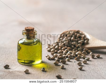 Hemp Seeds And Hemp Oil On Brown Wooden Table. Hemp Seeds In Wooden Spoon And Hemp Essential Oil In