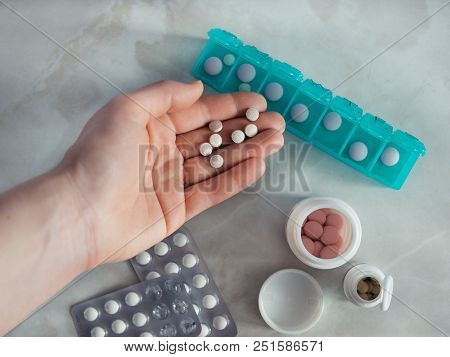 Hand With Pills And Pillbox. Top View Of Seven Day Pill Box With Pills. Green Pill-box Over Light Ma