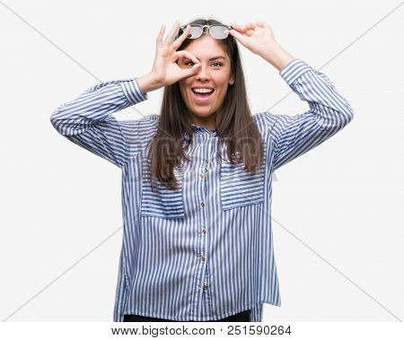 Young beautiful hispanic business woman doing ok gesture with hand smiling, eye looking through fingers with happy face.