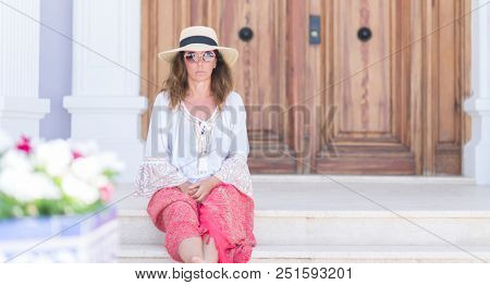 Middle age brunette woman wearing summer hat on vacations with a confident expression on smart face thinking serious